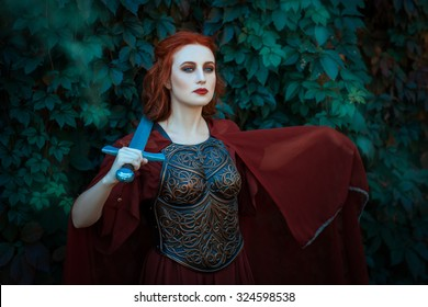 Red-haired girl warrior. In hands holds a sword on the chest wearing cuirass.