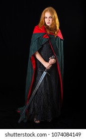 red-haired girl wearing in a black long gown and green cloak standing with knightly sword, on a dark background