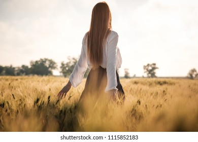 Red-haired girl in a wheat field at sunset. Beautiful woman in golden field at sunset, Backlit warm tones