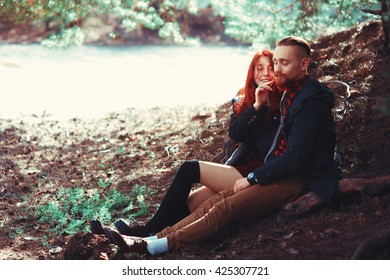 The red-haired guy with a beard and curly red-haired girl on the background of fabulous scenery of nature. Beautiful loving couple on a walk in the woods.