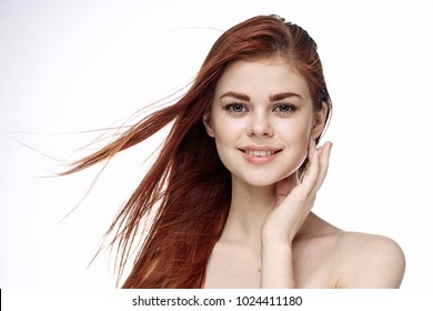 red-haired happy woman on a light background, beauty