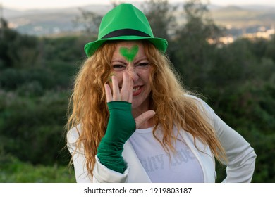 red-haired Irish woman in green cap on St. Patrick's Day