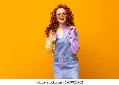 Red-haired lady in denim sundress and multi-colored sweatshirt laughs on orange background