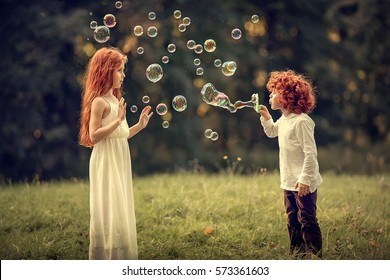 Red-haired little brother and sister are blowing bubbles during the sunset. Image with selective focus and toning