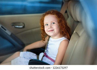 red-haired little girl in the car in the child seat.