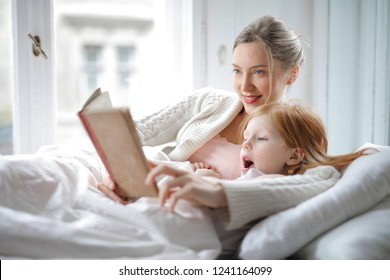 Red-haired little girl with her mom reading in bed.