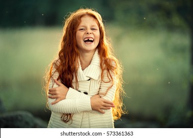 Red-haired little girl is laughing. There are a few holes in her mouth, she has lost her baby teeth. Image with selective focus and toning