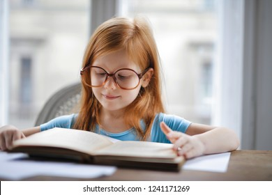 Red-haired little girl reading at home.