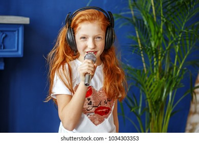 A red-haired little girl sings a song. The concept is childhood, lifestyle, music, singing, listening, hobbies.