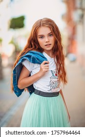 Red-haired little girl walks around the city in fashionable bright clothes. Children's clothing and footwear. Shopping