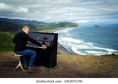 Red-haired man in a black sweater and jeans stands near an old black piano on a hill on the shore of the Pacific Ocean on the Kamchatka Peninsula. Art and music, people, travel and tourism concept.