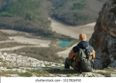 Red-haired man in a brown-and-blue windbreaker with green backpack sits on the slope of Mangup plateau in Crimea. Blurred spring forest is visible in valley in the background.