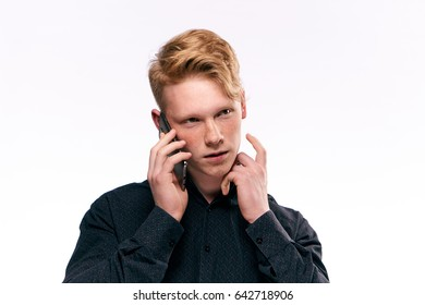 Red-haired man with freckles posing in front of camera