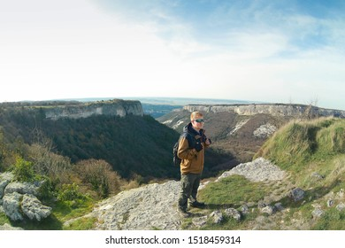 Red-haired man in sunglasses and a brown-and-blue windbreaker with green backpack stands on the top of Mangup plateau in Crimea. Crimean mountains are visible in the background.