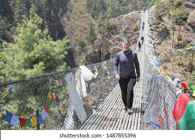 Red-haired man walking on a suspension bridge hanging over a canyon in Sagarmatha national park near Namche Bazaar town in Nepal. People, transportation, outdoors, travel and tourism concept.