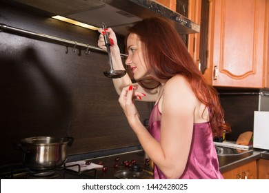 Red-haired middle-aged woman in the kitchen preparing food in a saucepan. Housewife tries food with a ladle
