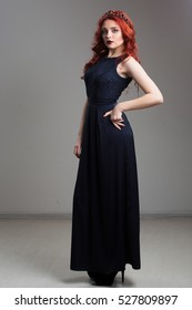 red-haired model posing in evening dress and in diadem