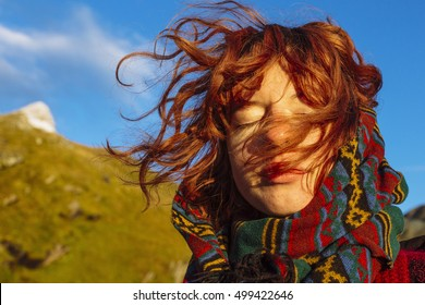 Red-haired, nice, calm girl standing and smiling in the sunrise, with the wind in her hair.