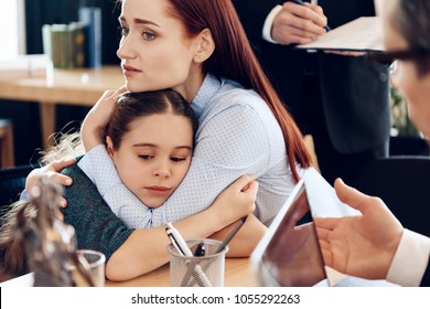 Red-haired sad woman hugs little upset girl sitting in lawyer's office for divorce. Two parents fighting over child in divorce concept.