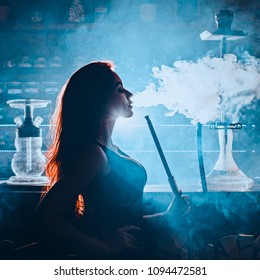 Red-haired sexy girl dressed in swimsuit and cap smoking a hookah. Toned image. Concept of pleasant spending time and female beauty. girl smokes hookah standing next to a hookah bar close up view