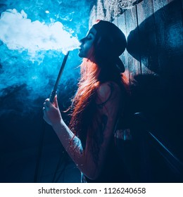 Red-haired sexy girl dressed in swimsuit and cap smoking a hookah. Toned image. Concept of pleasant spending time and female beauty. girl smokes hookah standing against the wall square cropping
