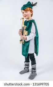 red-haired six years old boy on a neutral background, dressed as Robin Hood and holding a bow and arrow