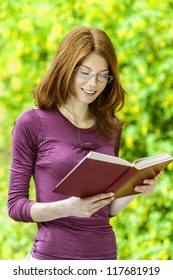 Red-haired smiling beautiful young woman with glasses reading book, against green of summer park.