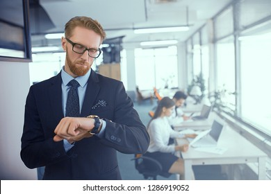 Red-haired solid man with glasses and a black suit checks the time on the clock. The superintendent controls the working hours of his subordinates