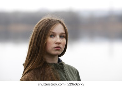The red-haired sweet and beautiful girl with freckles walks in autumn forest near the lake on the bridge