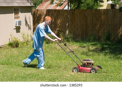 Red-haired teenaged boy mowing the lawn on a bright summer day.