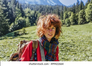 Red-haired, teenager girl with a scarf is standing and smiling in the sun rays in mountains, with the wind in her hair. Swiss alps, Switzerland.