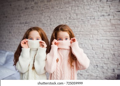 the red-haired twins hiding in knitted sweaters
