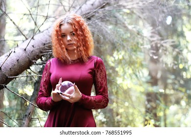The red-haired witch holds a ritual with a crystal ball in the forest