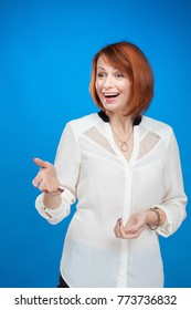 red-haired woman actress model in white blouse posing on blue background