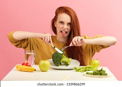 Red-haired woman in bad temper keeping strict vegetarian diet being tired of restrictions and hates greenery. Teenage girl holds broccoli on fork while making disgusting grimace, tongue sticking out