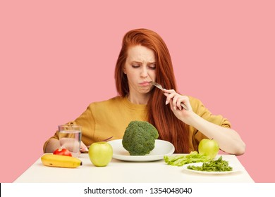 Red-haired woman in bad temper keeping strict vegetarian diet being tired of restrictions and hates greenery. Teenage girl holds broccoli on fork while making disgusting grimace,