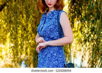 Red-haired woman in a blue dress on the background of nature with a leather bag on her shoulder check the time and looks at the wristwatch. The modern concept of bines and ginseng style.