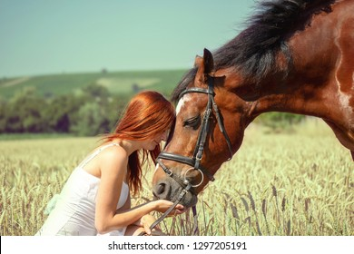 red-haired woman with brown horse in field in nature on meadow in summer in sunshine