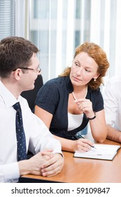 Red-haired woman communicating with his business colleague during meeting in board room. Happy man in glasses smiling and looking at her indoors.