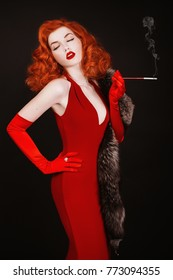 Red-haired woman with curly hair in red dress and long gloves smoke on black background. Girl is dressed in retro style with natural fur and the mouthpiece hand with white teeth