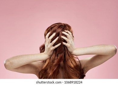 red-haired woman holding hands on head