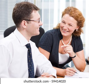 Red-haired woman laughing to his business colleague during meeting in Hi Res. Handsome man laughing to her and listening to her very attentively.