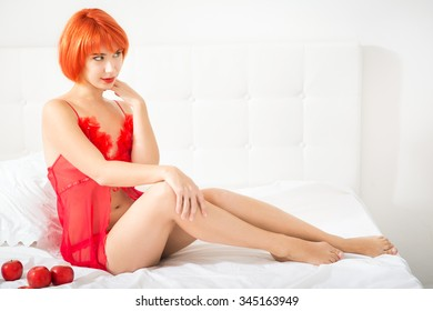 Red-haired woman in lingerie on the bed