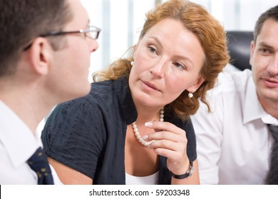 Red-haired woman listening to his colleague during meeting in Hi Res. People sitting at the table and discussing several burning issues indoors.