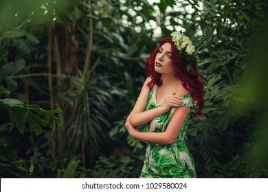 red-haired woman looking to the side on the background of a tree, park, nature