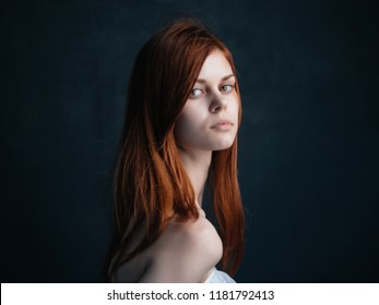 red-haired woman on a gray background bare shoulders