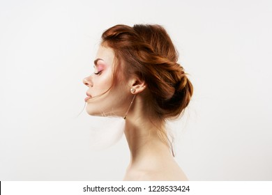 red-haired woman on a light background in earrings side view