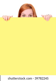 A red-haired woman peeks over the top of a yellow wall, with only her fingers and the top half of her head visible. Vertical format.