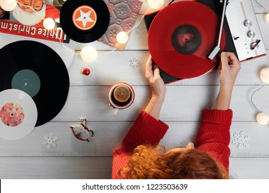 Red-haired woman puts a turntable stylus on red vinyl against the background of white wooden boards decorated cup with hot tea with lemon, Christmas lights, Christmas toys. Play Christmas tunes. Bokeh