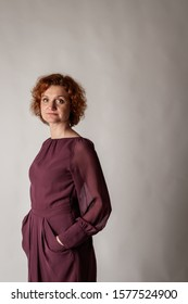 Red-haired woman. Red Hair woman on gray background. Serious woman.